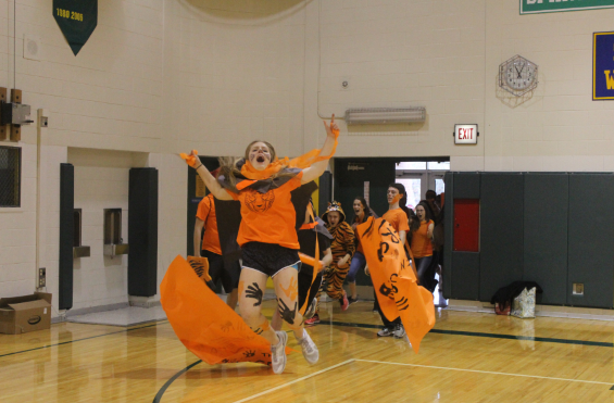 Nichole Geist, a Tiger House senior, ran through the Tiger's banner at Opening Ceremony.
